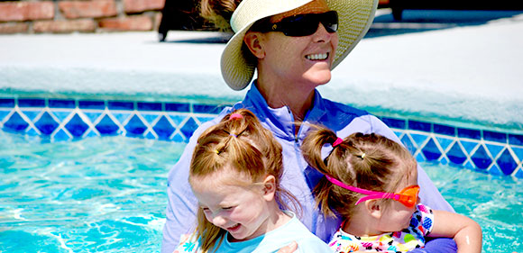 smiling kids being held by instructor in pool