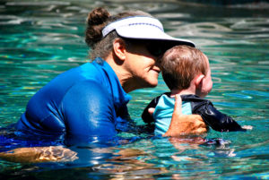 swim instructor holding baby in pool