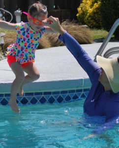 little girl jumping in pool